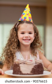 Smiling girl with a slice of cake in front of her