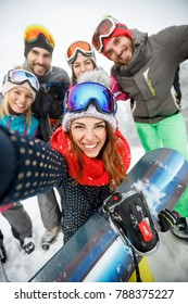Smiling girl with snowboard and friends on skiing