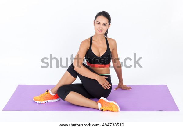 Smiling girl in sport clothes stretching up her muscles on a light purple mat. Concept of fitness and active lifestyle. Mock up.