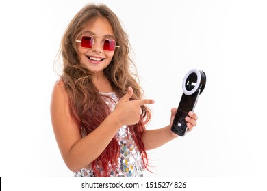Smiling girl in square red sunglasses holding black cellphone light-emitting-diode for selfie and pointing at it isolated