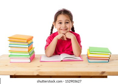Smiling girl with stack of books on the desk, isolated on white