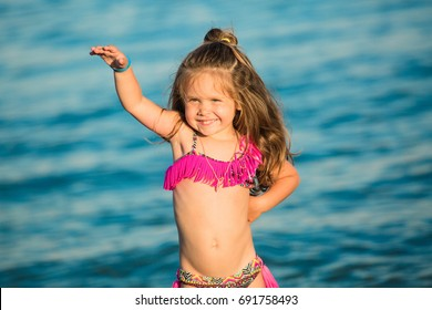 Smiling girl standing near the sea and dancing
