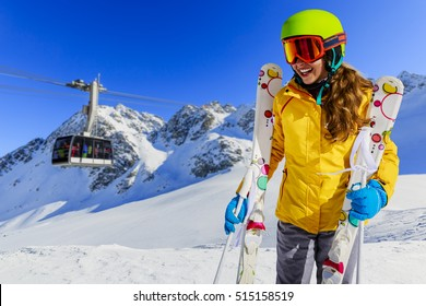 Smiling girl standing with ski and arms spreading wide open on the fresh powder snow at sunny day in mountains. Ski lift cable car in background. Switzerland, Verbier, Alps.