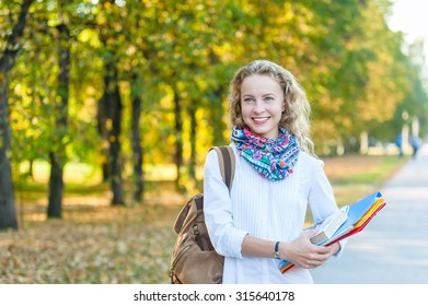 Smiling girl student with folders and books walking in the autumn park