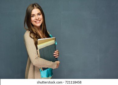 Smiling girl student or woman teacher portrait on gray wall.