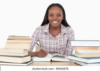 Smiling girl studying against a white background