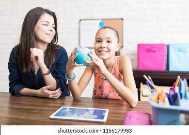 Smiling girl studying planet Earth by private teacher at home