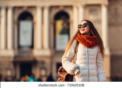 Smiling girl in sunglasses wears white down jacket and a orange scarf on the background of old blurred building. Tourism, happiness, trip concept