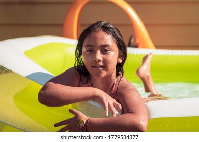 Smiling girl in swimming pool is looking at camera. A backyard pool party at home with kids.