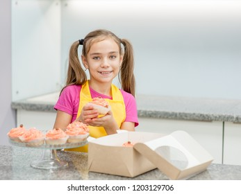 Smiling girl takes out the capcake from the gift box