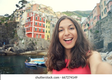 Smiling girl taking selfie photo in Riomaggiore, Cinque Terre, Italy. Vintage filter.