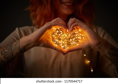 A smiling girl with a tattoo is holding in her hands a bright garland in the shape of a heart around a dark background. Happy Valentine's Day
