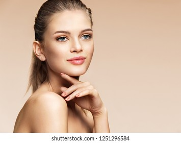 Smiling girl touching her face. Photo of girl with flawless skin on beige background. Skin care and beauty concept