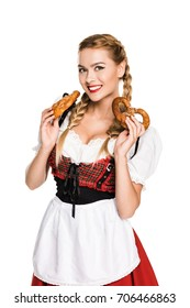 smiling girl in traditional german costume holding pretzels, isolated on white