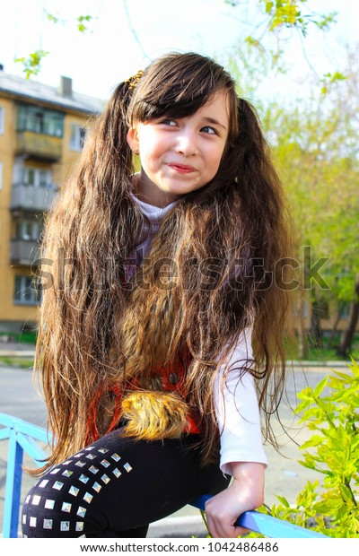 Smiling girl with two long tails of hair