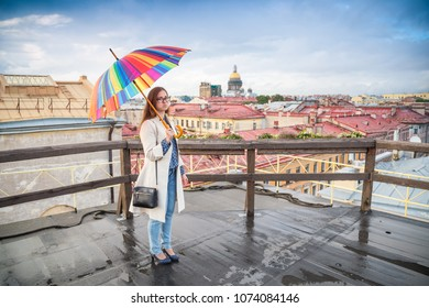 smiling girl with umbrella on the roof of the building