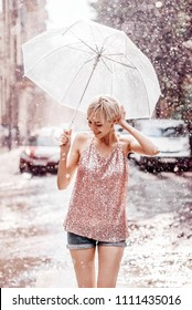 Smiling girl with umbrella posing under rain in street of the city