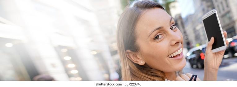 Smiling girl using phone in Manhattan street, template