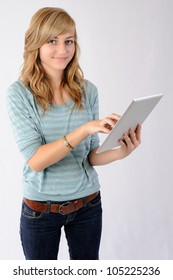 Smiling Girl Using Tablet Computer. Thirteen year old girl smiling at the viewer as she uses a tablet computer. Note: Not Isolated.