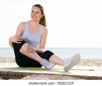 Smiling girl using various poses during regular training on beach
