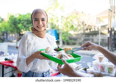 smiling girl in a veil give a plastic tray of takjil food to seller at a roadside stall