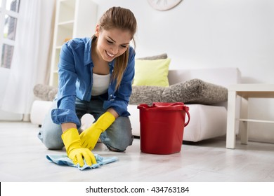Smiling girl wash the floor with rag and detergent