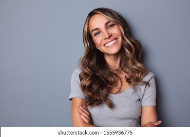 Smiling girl with wavy long hair. Portrait happy woman on gray background.