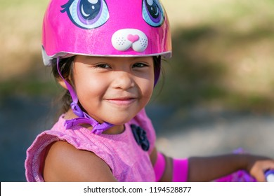 Smiling girl wearing cute pink bicycle helmet while learning to ride a bicycle during summer at a park