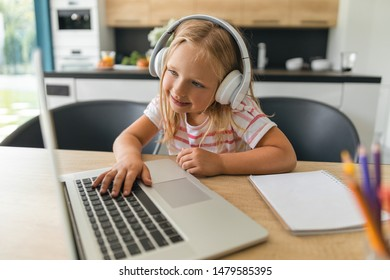 Smiling girl wearing headphones and looking at the laptop screen
