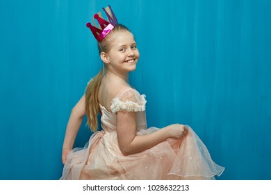 Smiling girl wearing pink dress dancing against blue wall background. Little princess with paper crown.