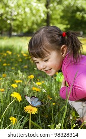 A smiling girl wearing a pink shirt, sitting on the dandelion field and observing a butterfly