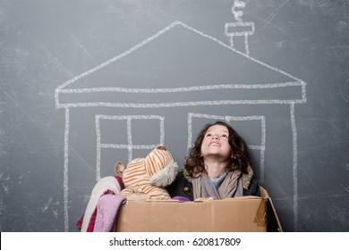 Smiling girl wearing shabby clothes in a paper box. Looking upwards, an old toy, grey background. Orphan dreams to have home.