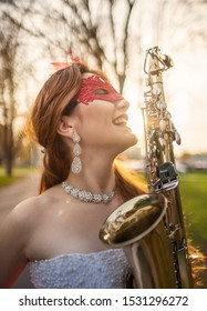 A smiling girl in a wedding dress with a red lace mask on background of autumn park with a saxophone in profile.