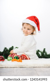 smiling girl in white dress sitting with christmas balls