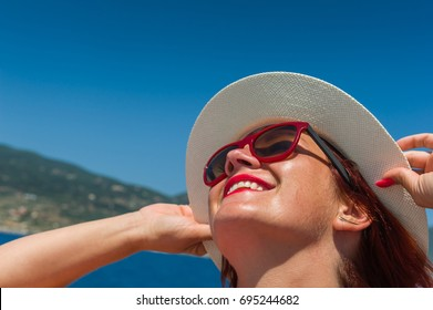 Smiling girl with white hat and sunglasses. Blue sea and Greece island in background.