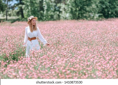 A smiling girl in a white polka dot dress and a hat in a soft pink flowering field of sainfoin.
