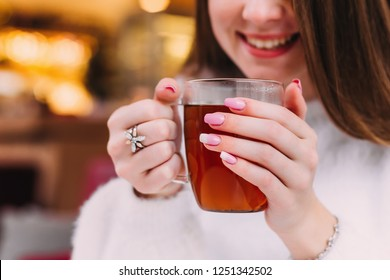 Smiling of girl who holding a transparent cup of tea in her hands