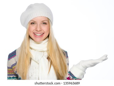 Smiling girl in winter clothes presenting something on empty hand