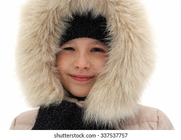 Smiling girl in winter on the street on a background of snow.