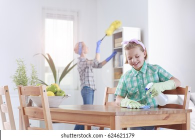 Smiling girl wiping the table in a dining room