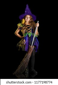 Smiling girl in a witch halloween fancy dress holding the broom against black background