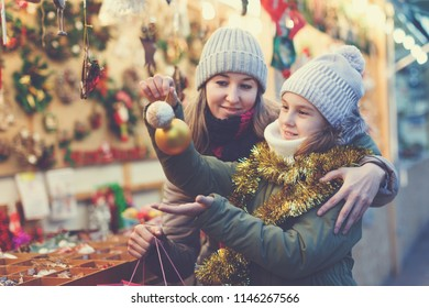Smiling girl with woman are buying toys for X-mas tree in the market outdoor.