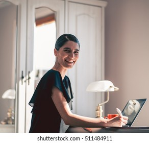 smiling girl working at desk. quiet room and a portrait of a beautiful woman with laptop