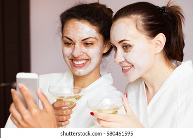 Smiling girlfriends with champagne and smartphone in the spa salon