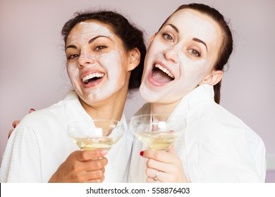 Smiling girlfriends with champagne in the spa salon