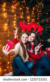 Smiling girlfriends taking a selfie with smarphone. Christmas mood.