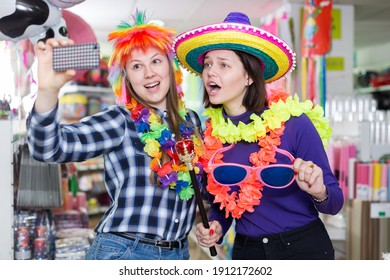 Smiling girls fooling around and taking selfie during shopping in store of festival outfits and accessories .