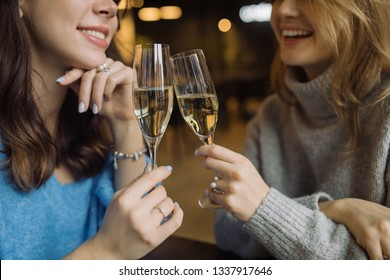 Smiling girls holding glasses of prosecco and making cheers in cafe. Celebration  concept.