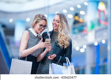 Smiling girls with mobile in a store
