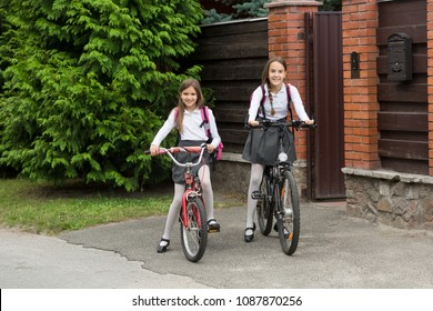 Smiling girls in school uniform riding to school on bicycles